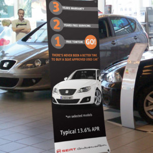The low cost X frame banner stand in use in a car show room with a promotional graphic in place